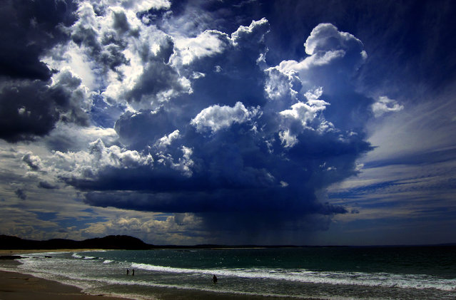 A giant storm cloud can be seen in the sky above swimmers near Mollymook Beach, south of Sydney, March 5, 2014. (Photo by David Gray/Reuters)