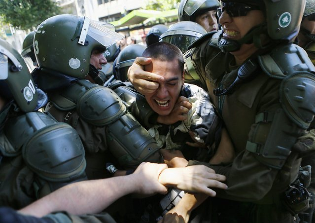 A student is detained during a demonstration near the Ministry of Education at Santiago, December 18, 2014. Students were protesting on Thursday against the increase in tariffs at their universities. (Photo by Ivan Alvarado/Reuters)