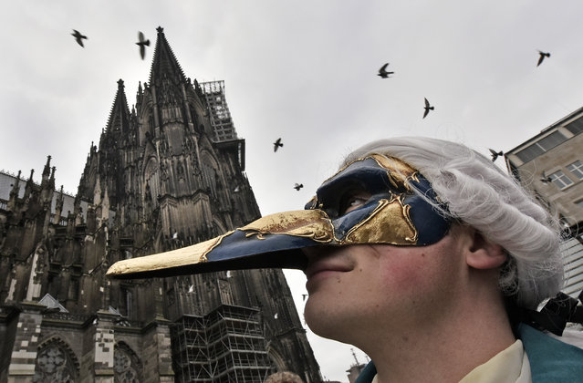 A dressed reveler looks up to the famous cathedral in Cologne, Germany, Wednesday, November 11, 2015. Thousands of carnival supporters celebrate the traditional beginning of the carnival season in Germany. (Photo by Martin Meissner/AP Photo)