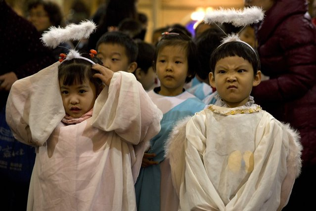 Children dressed as angels take part in a mass on the eve of Christmas at the South Cathedral official Catholic church in Beijing, China, Wednesday, December 24, 2014. Estimates for the number of Christians in China range from the conservative official figure of 23 million to as many as 100 million by independent scholars, raising the possibility that Christians may rival in size the 85 million members of the ruling Communist Party. (Photo by Ng Han Guan/AP Photo)