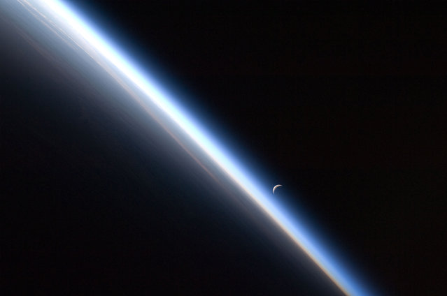 A full moon is visible with part of the International Space Station's solar array wing in this view above Earth's horizon, photographed by a crew member from the International Space Station while Space Shuttle Discovery (STS-128) remains docked with the station in this NASA handout photo taken September 3, 2009. (Photo by Reuters/NASA)