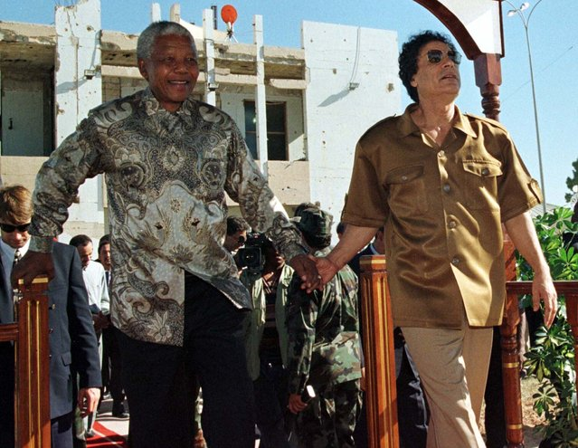 South Africa's President Nelson Mandela (L), defying U.S. objections to his visit, walks with Libyan leader Muammar Gaddafi October 22, 1997 in Tripoli. (Photo by Juda Ngwenya/Reuters)