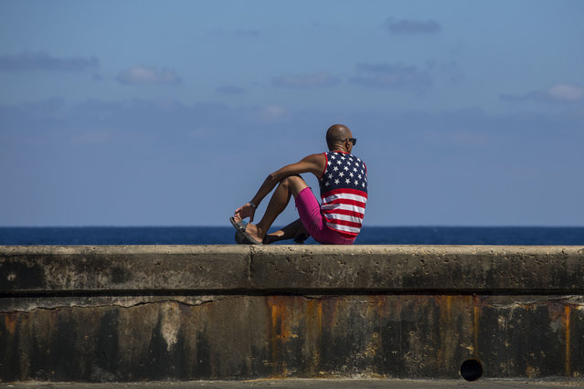 A man wearing a shirt with the stars and stripes sits on the Malecon in Havana, Cuba, Wednesday, April 18, 2018. Cuba's legislature opened today a two-day session that is to elect a successor to President Castro. (Photo by Desmond Boylan/AP Photo)