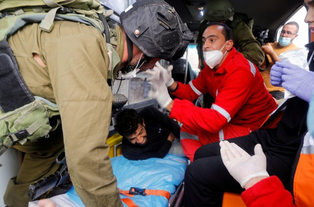 An Israeli soldier attempts to detain a wounded Palestinian demonstrator lying in an ambulance during a protest against Jewish settlements in Jordan Valley in the Israeli-occupied West Bank on November 24, 2020. (Photo by Raneen Sawafta/Reuters)