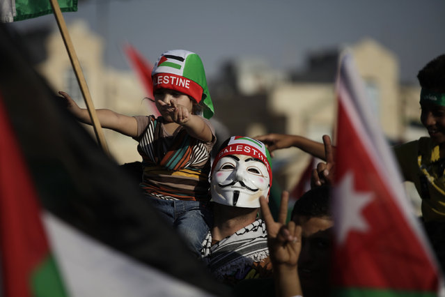 """Jordan: A man wears a Guy Fawkes mask and carries his daughter  during a celebration by the Muslim Brotherhood movement to declare victory of Gaza and Hamas against Israel, in Amman, Jordan, Friday, Aug. 29, 2014. Thousands of followers and supporters of the Muslim Brotherhood movement in Jordan celebrate what they call """"Hamas' Victory"""" against Israel. (Photo by Mohammad Hannon/AP Photo)"""