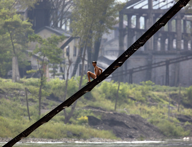 A North Korean man comes down a ladder in front of a disused factory along the banks of the Yalu River near the North Korean town of Qing Cheng, located around 50 kilometres north of the Chinese border city of Dandong September 12, 2008. (Photo by David Gray/Reuters)