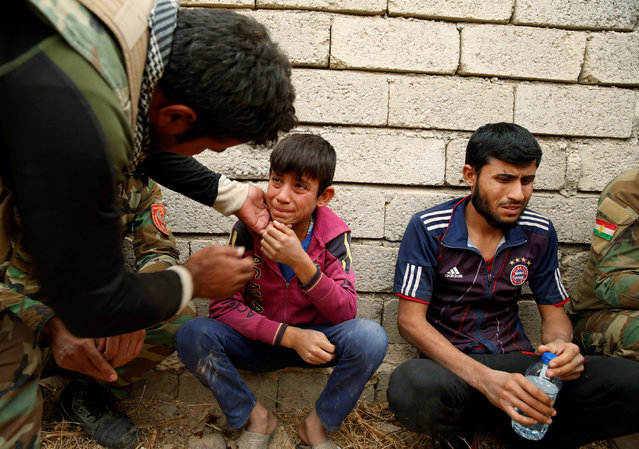 Ismail, an Iraqi boy who managed to escape from the Islamic State-controlled Jarbuah village near Mosul and arrived at the Kurdish Peshmerga military camp, breaks down in tears while recalling his experience, in Iraq October 28, 2016. (Photo by Ahmed Jadallah/Reuters)