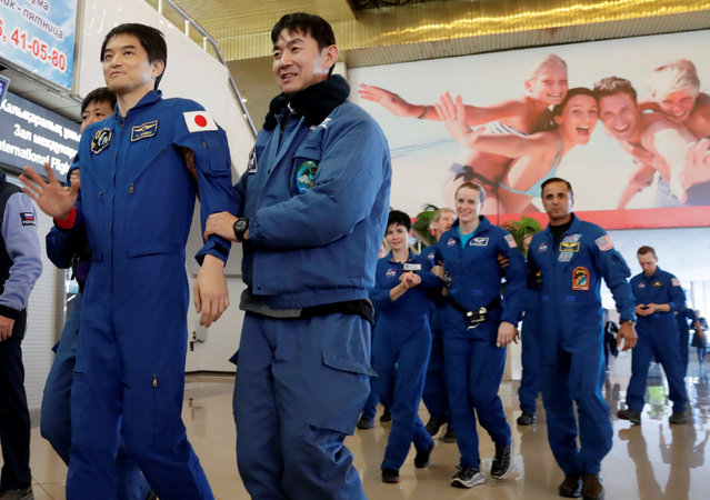 International Space Station (ISS) crew members Takuya Onishi of Japan and Kate Rubins of the U.S. are assisted by Japan Aerospace Agency (JAXA) and NASA space agency specialists at the airport in Karaganda, Kazakhstan, October 30, 2016. (Photo by Dmitri Lovetsky/Reuters)