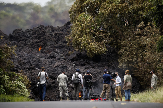 Members of the media record a wall of lava entering the ocean near Pahoa, Hawaii, Sunday, May 20, 2018. Kilauea volcano, oozing, spewing and exploding on Hawaii's Big Island, has gotten more hazardous in recent days, with rivers of molten rock pouring into the ocean and flying lava causing the first major injury. (Photo by Jae C. Hong/AP Photo)