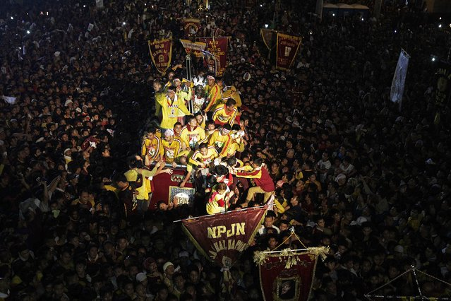 Devotees welcome the Black Nazarene as it is pulled on a carriage toward the entrance of a Catholic church after a 19-hour procession in Manila January 10, 2015. (Photo by Erik De Castro/Reuters)