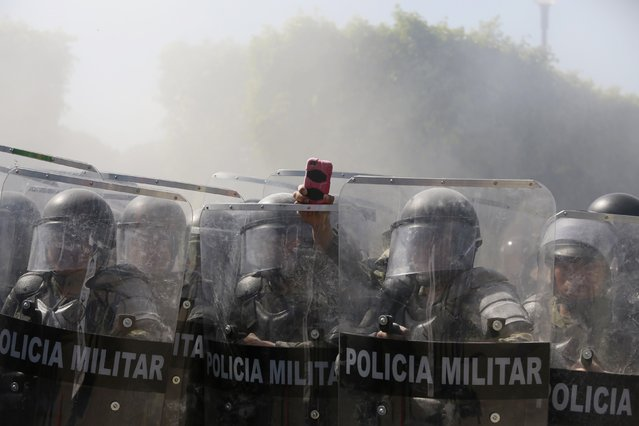 A military police officer records with a cell phone, amid smoke, during a demonstration by activists and relatives of the 43 missing trainee teachers from Ayotzinapa Teacher Training College, in the military zone of the 27th infantry battalion, in Iguala, Guerrero, January 12, 2015. (Photo by Jorge Dan Lopez/Reuters)