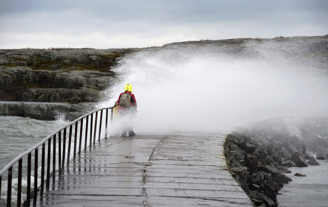 A woman is hit by a wave caused by stormy winds in Helsinki, on November 30, 2015. (Photo by Markku Ulander/AFP Photo)