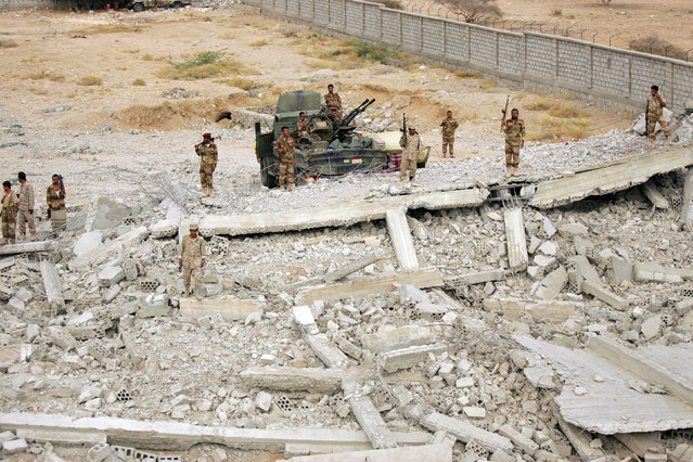 Yemeni soldiers stand on the ruins of a machine gun mounted on a truck at the site of a police barracks, which was bombed by al Qaeda insurgents, in al-Mahfad in the southern Yemeni province of Abyan May 23, 2014. (Photo by Khaled Abdullah/Reuters)