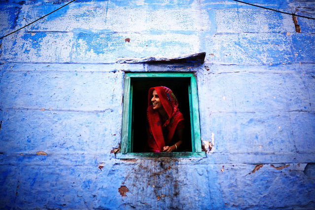 """""""Indian Smiles"""". She opens the window and feels so curious about the new Chinese faces in the old Jodhpur streets around her house. What a beautiful saree and pretty smile! (Photo and caption by Mac Kwan/National Geographic Traveler Photo Contest)"""