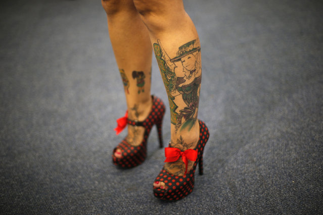 A woman exhibits her tattoos and red polka dot shoes during Rio Tattoo Week in Rio de Janeiro, Brazil, Friday, January 16, 2015. (Photo by Silvia Izquierdo/AP Photo)