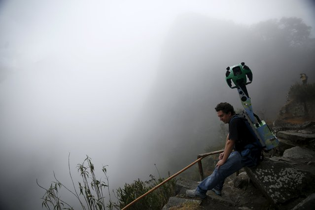 A trekker Operator takes a rest carryingthe Trekker, a 15-camera device, while mapping the Inca citadel of Machu Picchu for Google Street View in Cuzco, Peru, August 12, 2015. (Photo by Pilar Olivares/Reuters)