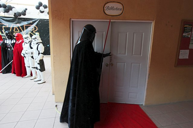 A person dressed as the character of Darth Vader opens a door during a Star Wars fan convention in Ciudad Juarez, December 5, 2015. (Photo by Jose Luis Gonzalez/Reuters)