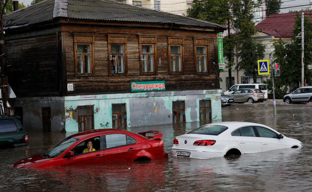 "This absolute hero came to the rescue when flash floods in a World Cup city left two women stranded in their submerged cars. Fans in Nizhny Novgorod in western Russia have been basking in sunshine on the banks of the Volga river since the World Cup began. But the lovely weather was put on ice when the heavens opened and a thunderstorm flooded the medieval city. It only took half an hour for the heavy rain to quickly build up rivers of water, bringing traffic to a standstill and stranding motorists. But one man, dressed in a smart shirt and tie, leapt into action to rescue two women from their cars. Pictures show him wading in the waist-high water, dragging them out of their car windows one by one, and carrying them to safety. Due to the presence of a less-than-perfect drainage system, the water quickly rose to dangerous levels. While the flooding briefly dampened spirits at a hilltop fan zone, the sun soon came out again, calm returned, and locals simply shook their heads. ""It's not the first time – we're used to it"", said one shopkeeper, watching motorists open their bonnets to let their engines dry out. Here: A woman uses her phone as she sits in the car at the flooded street in Nizhny Novgorod, Russia on June 19, 2018. (Photo by Murad Sezer/Reuters)"