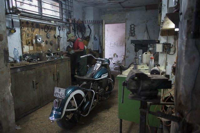 Mechanic Wilfredo Medino, 59, fixes a Harley Davidson motorbike inside a garage in downtown Havana January 15, 2015. (Photo by Alexandre Meneghini/Reuters)