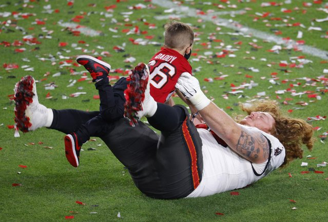 Ryan Jensen #66 of the Tampa Bay Buccaneers celebrates with his child after defeating the Kansas City Chiefs in Super Bowl LV at Raymond James Stadium on February 07, 2021 in Tampa, Florida. The Buccaneers defeated the Chiefs 31-9. (Photo by Brian Snyder/Reuters)