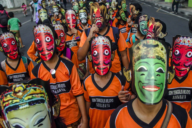 Indonesian students wearing paper masks take part in the East Java Mask Parade in Surabaya, Indonesia, 13 December 2015. Thousands of people participate in the traditional parade to preserve the mask custom among the younger generation. (Photo by Fully Handoko/EPA)