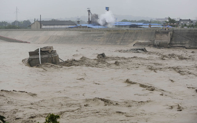 In this photo provided by China's Xinhua News Agency, a collapsed bridge over the Panjiang river is seen in Qinglian, Jiangyou city, southwest China's Sichuan Province, Tuesday, July 9, 2013. The official Xinhua News Agency said one sedan car, three minivans and one SUV fell into the torrent when the more than 40-year-old Qinglian bridge broke apart just before noon in the city.  Three people were pulled from the raging river but six other remained missing following the bridge collapse Tuesday. (Photo by Li Qiaoqiao/AP Photo/Xinhua)