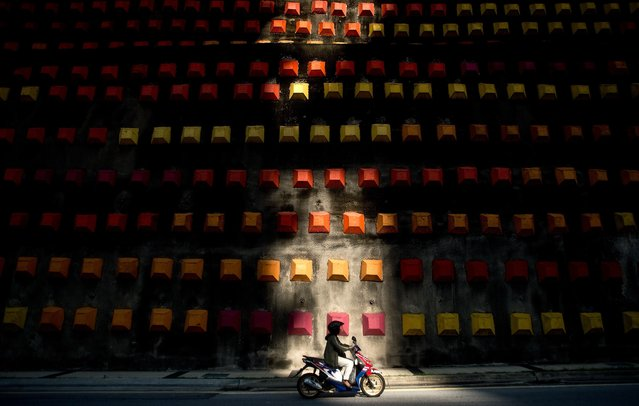 A motorist rides to work past a decorated wall in Kuala Lumpur on May 6, 2014. According to a Michingan University report earlier this year, Malaysia is ranked among the top 20 most dangerous countries for road users. (Photo by Manan Vatsyayana/AFP Photo)