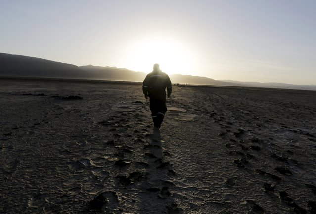 A man walks on the dried Poopo lakebed in the Oruro Department, south of La Paz, Bolivia, December 17, 2015. (Photo by David Mercado/Reuters)