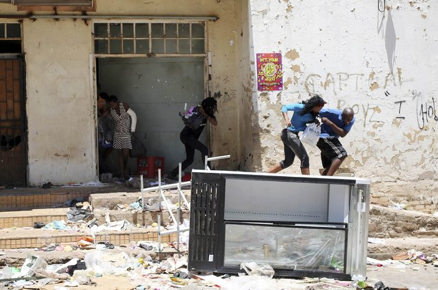 Locals react as they are shot at by a policeman (not in the picture) while looting from a shop, believed to be owned by a foreigner, during service delivery protests in Mohlakeng, west of Johannesburg February 4, 2015. (Photo by Siphiwe Sibeko/Reuters)