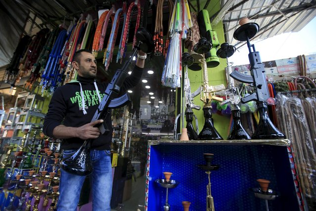 A vendor displays hookahs shaped like rifles inside a souk at the port city of Sidon, southern Lebanon, December 23, 2015. (Photo by Ali Hashisho/Reuters)