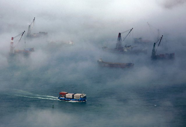 A container ship sails past barges during foggy conditions at Hong Kong's Victoria Harbour in this March 15, 2010 file photo. Sentiment at some of Asia's biggest firms deteriorated again in the fourth quarter, falling to a four-year low under the weight of concerns about slowing growth in China, the region's biggest economy, a Thomson Reuters/INSEAD survey showed. (Photo by Bobby Yip/Reuters)