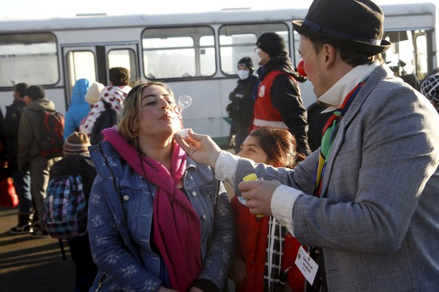 A member of Clown Doctors Red Noses entertains migrants before their departure to Austria at a registration center in Dobova, Slovenia, December 27, 2015. (Photo by Srdjan Zivulovic/Reuters)