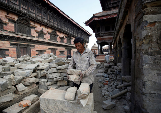 A man collects stones from a collapsed temple as he works to rebuild a temple damaged during the 2015 earthquake, in Bhaktapur, Nepal November 23, 2016. (Photo by Navesh Chitrakar/Reuters)