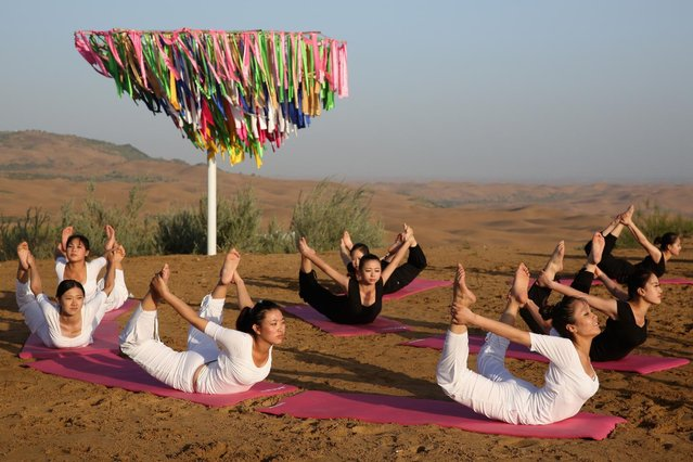 Dancers perform yoga in Xiangshawan Desert, also called Sounding Sand Desert on July 19, 2013 in Ordos of Inner Mongolia Autonomous Region, China. Xiangshawan is China's famous tourist resort in the desert. It is located along the middle section of Kubuqi Desert on the south tip of Dalate League under Ordos City. Sliding down from the 110-metre-high, 45-degree sand hill, running a course of 200 metres, the sands produce the sound of automobile engines, a natural phenomenon that nobody can explain. (Photo by Feng Li/Getty Images)