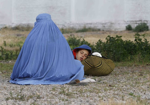 An Afghan refugee woman, clad in a burqa, sits with her sleeping boy as they wait with others to be repatriated to Afghanistan, at the United Nations High Commissioner for Refugees (UNHCR) office on the outskirts of Peshawar, February 2, 2015. (Photo by Fayaz Aziz/Reuters)