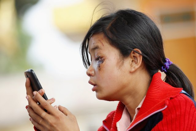 Hnin Thaphu Zaw, 14, uses a phone to contact her father, whose car crashed while they fleeing from Laukkai, the capital of Kokang in Shan State, as she arrives at a monastery as made refugee camp in Lashio February 16, 2015. (Photo by Soe Zeya Tun/Reuters)