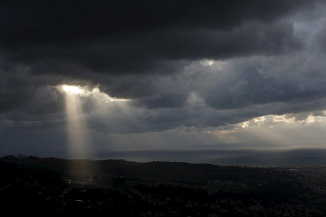 The sun shines through dark clouds hanging over al-Jamhour town in eastern Beirut, Lebanon, January 1, 2016. (Photo by Jamal Saidi/Reuters)