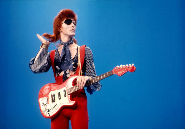 David Bowie wears an eyepatch in red suit and guitar on blue background at Top Pop television studios in Holland while doing playback to his hit song Rebel Rebel in 1974. (Photo by Barry Schultz/Sunshine/REX Shutterstock)