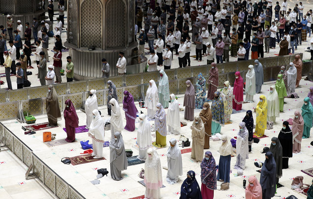 """Indonesian Muslims pray spaced apart as they practice social distancing to curb the spread of the new coronavirus during an evening prayer called """"tarawih"""" marking the first eve of the holy fasting month of Ramadan at Istiqlal Mosque in Jakarta, Indonesia. Monday, April 12, 2021. During Ramadan, the holiest month in Islamic calendar, Muslims refrain from eating, drinking, smoking and s*x from dawn to dusk. (Photo by Achmad Ibrahim/AP Photo)"""