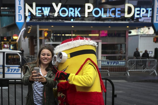 A child poses for a selfie with a Minion character dressed in a Christmas theme in Times Square during unseasonably warm weather on Christmas Eve in the Manhattan borough of New York December 24, 2015. (Photo by Carlo Allegri/Reuters)