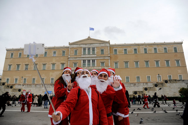 People dressed in Santa costumes take a selfie in front of the parliament building as they take part in the Santa Run Athens, in Athens, Greece, December 4,  2016. (Photo by Michalis Karagiannis/Reuters)