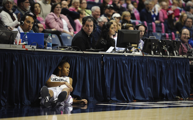 Connecticut's Moriah Jefferson lands under the media table after attempting a shot from half court at the end of the first half of an NCAA college basketball game against Tulane, Saturday, February 14, 2015, in Storrs, Conn. UConn won 87-39. (Photo by Jessica Hill/AP Photo)