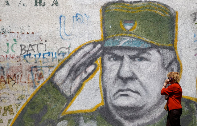 A woman walks past graffiti of Bosnian Serb wartime general Ratko Mladic in a suburb of Belgrade, Serbia, May 27, 2011. (Photo by Stoyan Nenov/Reuters)