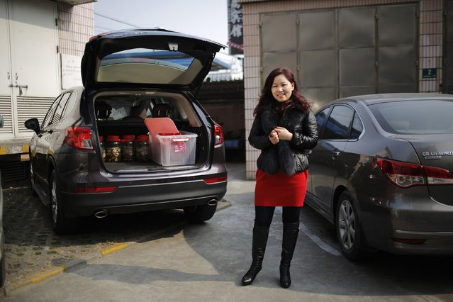 Yan Aimei poses for a portrait as she prepares to leave on a car trip for the upcoming Chinese New Year, in Shanghai, February 13, 2015. Yan and her family travelled to Jiangxi province by car to spend Chinese New Year with her family. (Photo by Carlos Barria/Reuters)