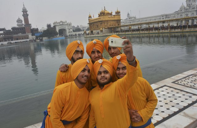 Sikh devotees take selfies on the eve of the birth anniversary of the tenth and final Sikh Guru, Gobind Singh, in Golden Temple, Sikh's holiest shrine in Amritsar, India, Friday, January 15, 2016. Gobind Singh is considered a forefather in the religion. (Photo by Prabhjot Gill/AP Photo)