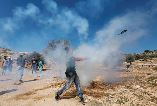 A Palestinian demonstrator hurls stones at Israeli troops during a protest against Israeli land seizures for Jewish settlements, in the village of Ras Karkar, near Ramallah in the occupied West Bank September 28, 2018. (Photo by Mohamad Torokman/Reuters)