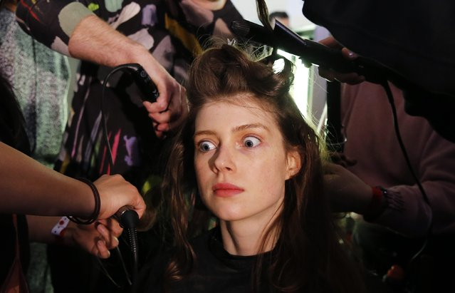A model reacts while getting her hair styled backstage before the presentation of the Hunter Autumn/Winter 2015 collection during London Fashion Week February 23, 2015. (Photo by Suzanne Plunkett/Reuters)