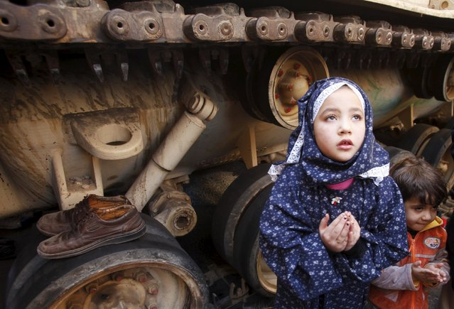 A girl attends Friday prayers in front of an army tank in Tahrir Square in Cairo February 18, 2011. (Photo by Suhaib Salem/Reuters)