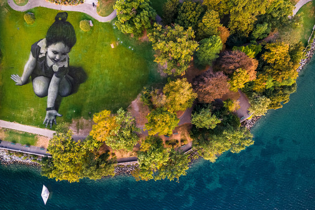 "A picture taken with a drone shows the giant landart painting entitled ""Message From Future"" by French artist Saype in the park ""La Perle du Lac"" in Geneva, Switzerland, 16 September 2018 (issued 17 September). The artwork covering 5,000 square meters was produced with biodegradable paints made from natural pigments. The artist called the little girl ""Future"" as a symbol of the generations from the future and the small origami boats that she drops into Lake Geneva aims to represent a message of hope sent to the world. (Photo by Valentin Flauraud/EPA/EFE)"