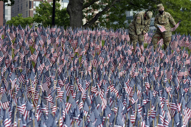 Master Sgt. Mark Radnick, and Capt. Ann Marie Leifer of the Mass. Air National Guard were among those planting American flags on Boston Common Wednesday, May 26, 2021, in Boston. Each year before Memorial Day weekend the Massachusetts Military Heroes Fund places a flag to represent every fallen member of the US military from Massachusetts since the Revolutionary War. (Photo by Josh Reynolds/AP Photo)